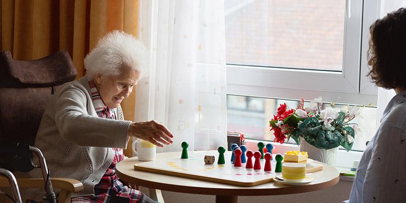 Alte Dame und Pflegerin spielen Schach