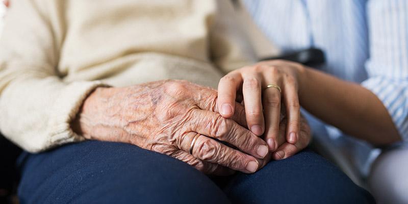 Gestaltungsbild: Alte Hände werden von jungen Händen umfasst