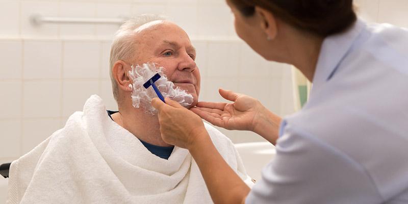 Gestaltungsbild: Pflegerin rasiert Pflegebedürftigen älteren Mann
