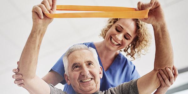 Gestaltungsbild: Pflegerin macht mit Mann Reha-Übung